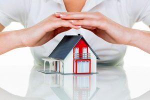 Eine Frau beschützt Ihr Haus und Eigenheim. Gute Versicherung und seriöse Finanzierung beruhigen.